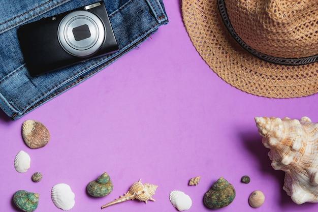 Ubrania, aparat fotograficzny, brązowy kapelusz, muszle na bzu