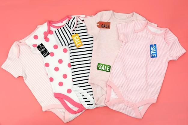 Ubrania dla dzieci i drewniane kostki na różowo.