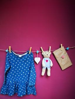 Ubrania dla dzieci i towary pusta notatka lub kartka z życzeniami i zabawka wisząca na spinaczach do bielizny na sznurku