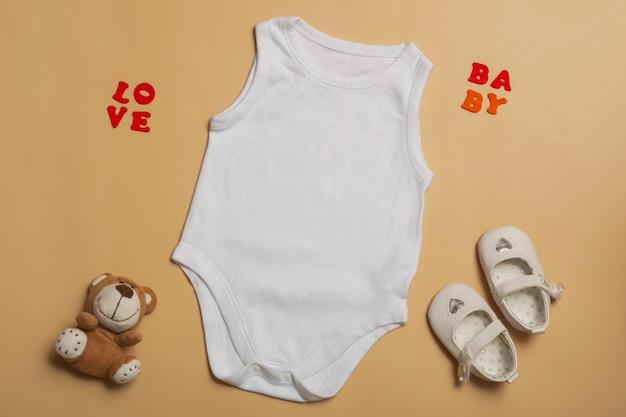 Ubrania dla dzieci makieta szablon pusty biały kombinezon dla noworodków, buty i misia na beżowym tle. miejsce na tekst, widok z góry