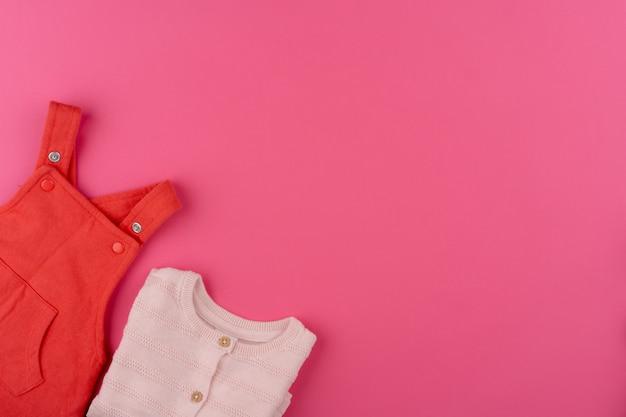 Ubrania dla dzieci na różowej powierzchni