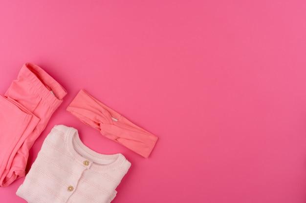 Ubrania dla dzieci na różowym powierzchni widok z góry