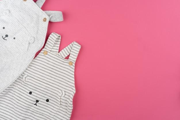 Ubrania dla dzieci na różowym tle widok z góry