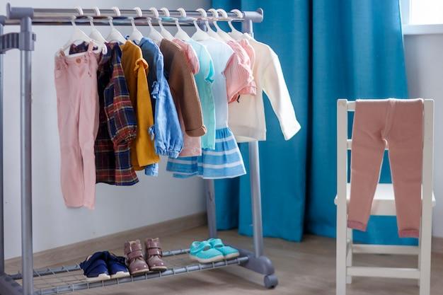 Ubrania dla małych pań wisiały w pokoju dziecięcym