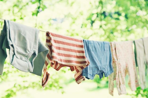 Ubrania dziecięce wiszące na sznurku na zewnątrz pranie dziecięce wiszące na sznurku na zielonym tle