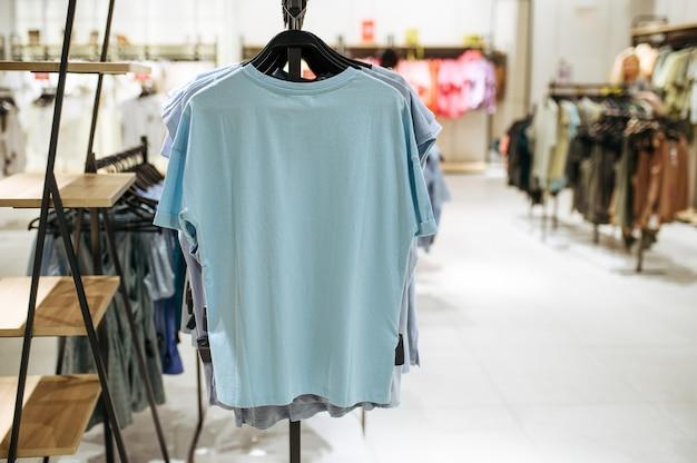 Ubrania na wieszakach w sklepie odzieżowym, nikt. sklep z modą lub wnętrze butiku, odzież w salonie