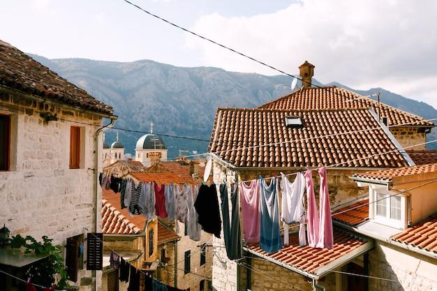 Ubrania są suszone na sznurze między budynkami na starym mieście w kotorze w czarnogórze