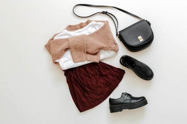Ubrania składane dla kobiet moda miejski podstawowy strój. kobiecy wygląd wiosna strój jesienny bordowa spódnica beżowy sweter czarna torba na buty biała koszulka na białym tle. widok z góry mundurek szkolny.