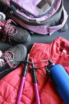 Ubrania turystyczne dla kobiet i mężczyzn, składające się z butów, plecaka, bidonu i laski