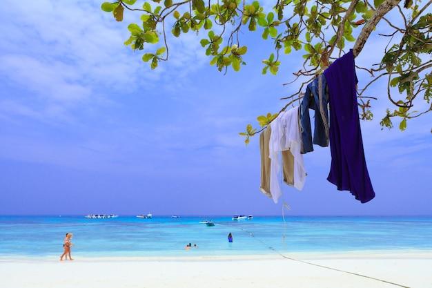 Ubrania turystyczne wiszą na gałęzi drzewa, plaża w południowej tajlandii