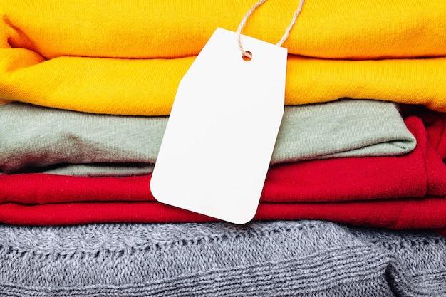 Ubrania w kupie, złożone w kupie jesiennych jasnych kolorach z pustą etykietą. modne jesienne kolory garderoby. miejsce na tekst.