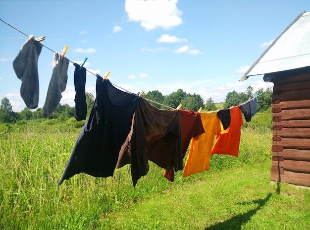Ubrania wiszące na linii prania na tle błękitnego nieba i zielonego pola. linia do prania z suszeniem ubrań na dziedzińcu.