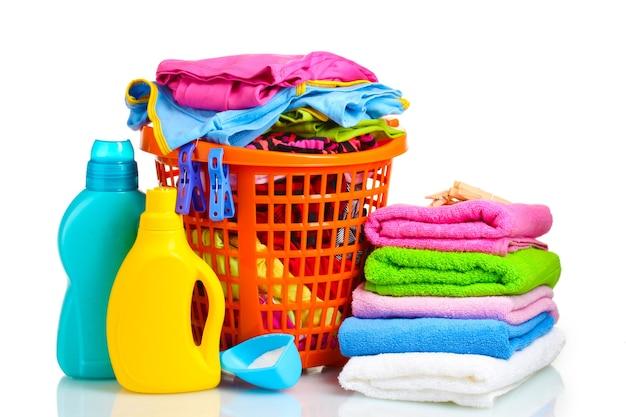 Ubrania z detergentem i proszkiem do prania w pomarańczowym koszu z tworzywa sztucznego na białym tle