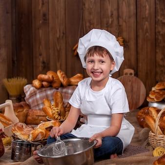 Ubrany jak kucharz dziecko zapobiega ubijaniu mąki baker dużo bułek