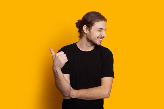 Ubrany w czarny kaukaski mężczyzna z długimi włosami i brodą jest skierowany w górę, uśmiechając się i pozując na żółtym tle