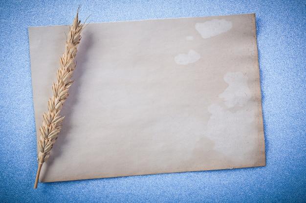 Ucho pszenicy vintage arkusz papieru na niebieskiej powierzchni