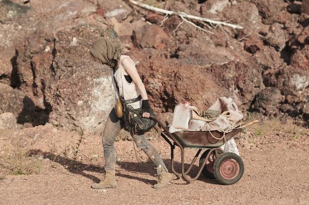 Uchodźczyni niosąca wózek z różnymi rzeczami podczas spaceru wzdłuż pustyni