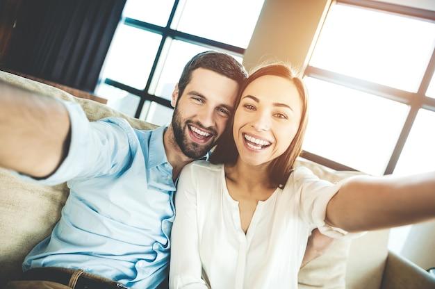 Uchwyć jasne chwile. piękna młoda kochająca się para, która łączy się ze sobą i robi selfie, siedząc razem na kanapie