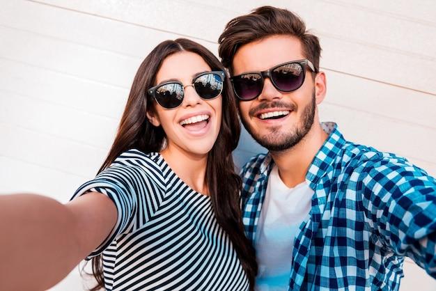 Uchwyć jasne chwile. radosna młoda kochająca para robi selfie przed kamerą stojąc na zewnątrz