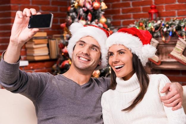 Uchwyć szczęśliwe chwile. piękna młoda kochająca się para, która łączy się ze sobą i uśmiecha podczas robienia selfie z choinką w tle