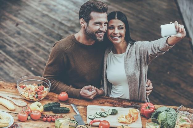 Uchwyć wspólne chwile. widok z góry na piękną młodą parę robi selfie i uśmiecha się podczas wspólnego przygotowywania jedzenia