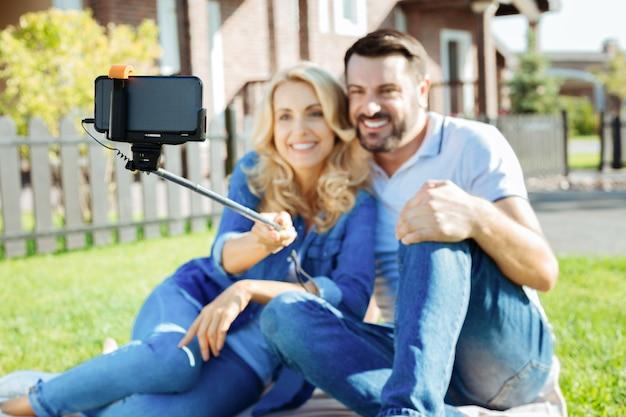 Uchwycenie chwil. skoncentruj się na kiju sefie w dłoniach pięknej kobiety siedzącej i wiążącej się z ukochanym mężem podczas wspólnego robienia selfie