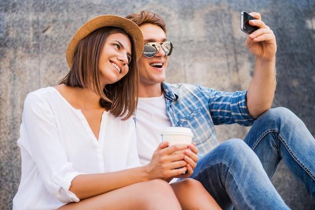 Uchwycenie jasnych chwil. szczęśliwa młoda para kochająca robi selfie za pomocą smartfona, opierając się o ścianę