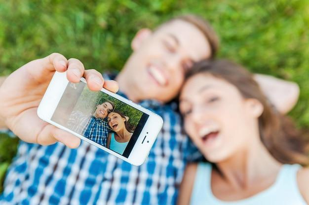 Uchwycenie jasnych emocji. widok z góry szczęśliwa młoda kochająca para co selfie z inteligentnego telefonu, leżąc na trawie.