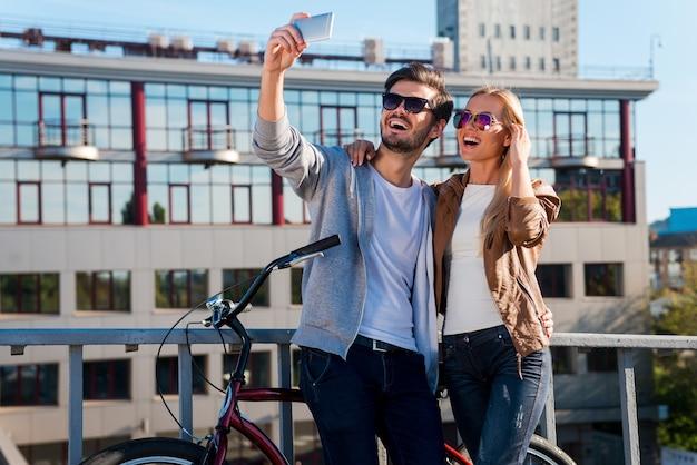 Uchwycenie miłości i zabawy. piękna młoda para robi selfie na swoim smartfonie i uśmiecha się stojąc w pobliżu roweru na świeżym powietrzu