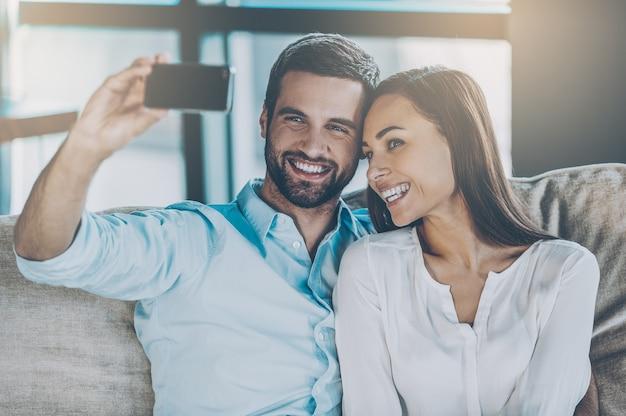 Uchwycenie miłości. piękna młoda kochająca się para, która łączy się ze sobą i robi selfie, siedząc razem na kanapie