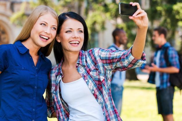 Uchwycenie szczęśliwej chwili. dwie piękne młode kobiety robią selfie, stojąc blisko siebie z dwoma rozmawiającymi mężczyznami w tle