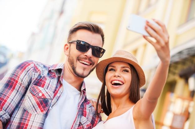 Uchwycenie szczęśliwej chwili. niski kąt widzenia szczęśliwej młodej kochającej się pary robi selfie stojąc razem na zewnątrz