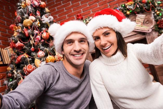 Uchwycenie szczęśliwej chwili. piękna młoda kochająca się para, która łączy się ze sobą i uśmiecha podczas robienia selfie z choinką w tle