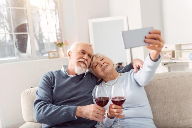 Uchwycenie szczęśliwej chwili. radosny starszy mąż i żona przytulają się na kanapie i robią selfie przy winie