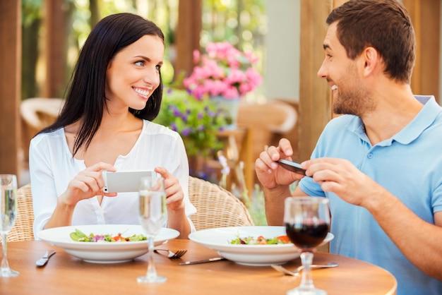 Uchwycenie wspólnego czasu. szczęśliwa młoda kochająca para robi zdjęcia jedzenia i uśmiecha się podczas wspólnego relaksu w restauracji na świeżym powietrzu