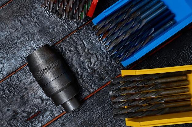 Uchwyt wiertarski i wiertła w kolorowych pudełkach na czarnej drewnianej powierzchni
