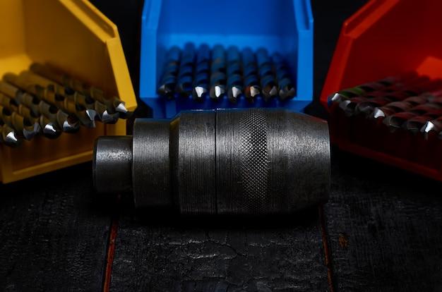 Uchwyt wiertarski i wiertła w kolorowych pudełkach na czarnym drewnianym stole