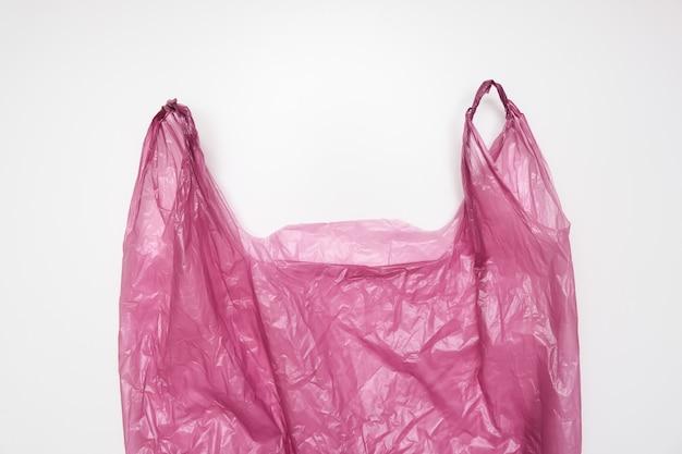 Uchwyty czerwonej plastikowej torby na białym tle.