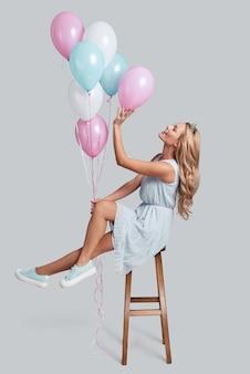 Ucieczka… pełnej długości studio ujęcie atrakcyjnej młodej kobiety w koronie trzymającej balony, unoszącej się w powietrzu na szarym tle