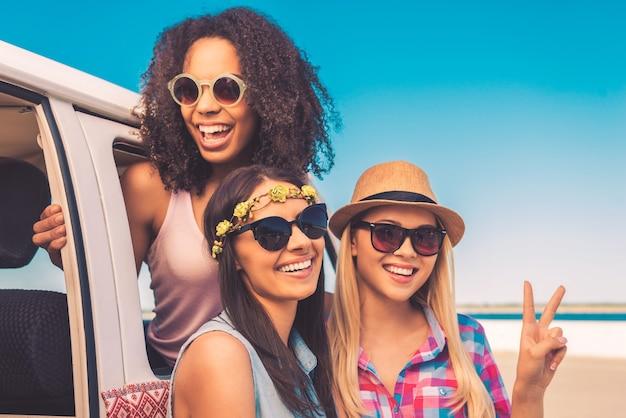 Uciekać z moimi dziewczynami. trzy wesołe młode kobiety pochylają się nad swoim minivanem i uśmiechają się