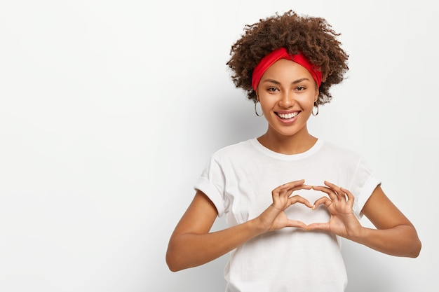 Ucieszona, zadowolona kobieta wykonuje gest serca, miło się uśmiecha, nosi swobodny strój, wyraża dobre uczucia kochankowi