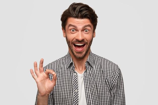 Ucieszony, szczęśliwy mężczyzna robi dobry gest, pokazuje, że wszystko jest w porządku, mówi, żeby być spokojnym, gestykuluje na białej ścianie