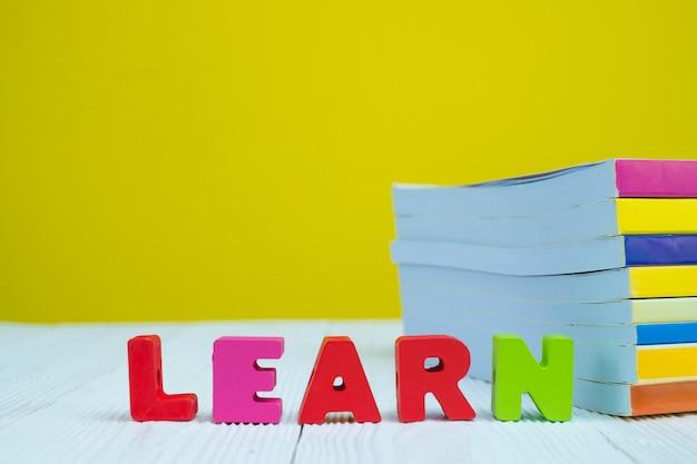 Ucz się alfabetu tekstu i stos książki na białym stole z żółtym tle.
