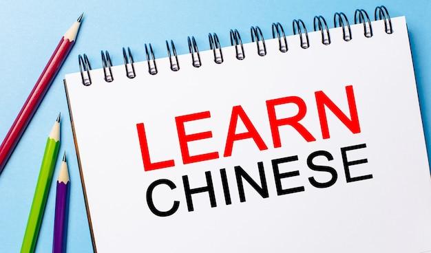 Ucz się chińskiego na białym notatniku z ołówkami na niebieskiej powierzchni