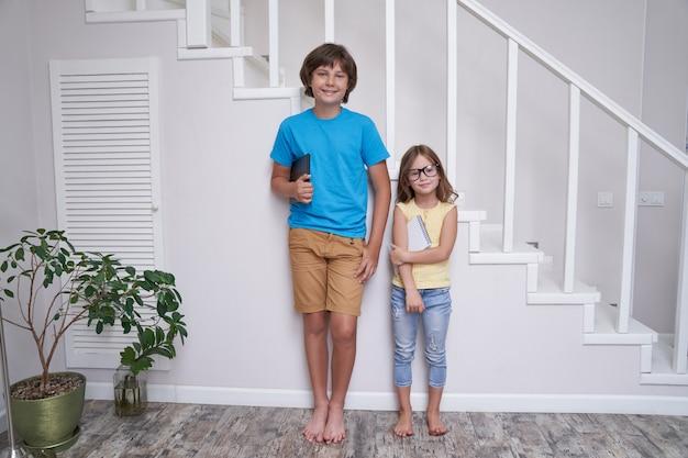 Uczący się w domu brat i siostra stoją przy schodach w domu, patrząc na kamerę i uśmiechając się po