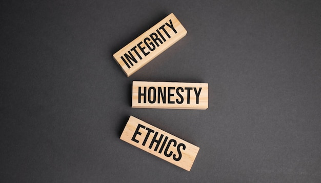 Uczciwość, uczciwość, etyka słowa na drewnianych klockach na żółtym tle. koncepcja etyki biznesu.