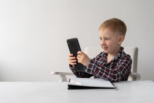 Uczeń blondyn siedzi na krześle przed stołem. kształcenie na odległość i kwarantanna. dziecko ma w rękach tablet i zeszyt do pisania na stole.