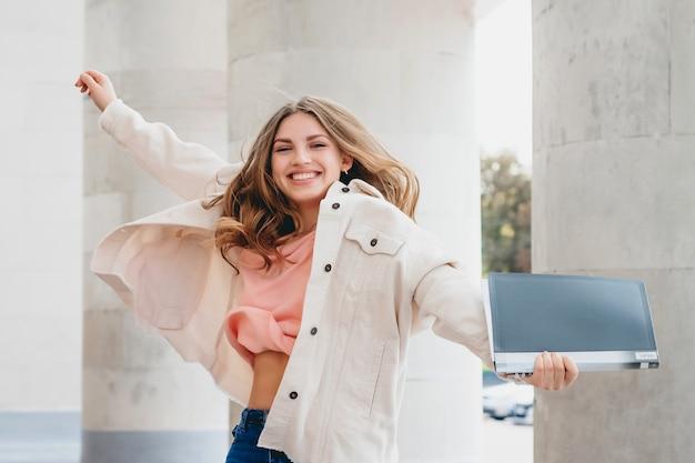 Uczeń blondynka skacze z radości. dziewczyna pomyślnie zdała egzamin, koncepcja edukacji