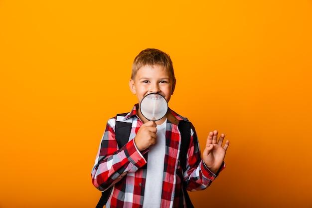 Uczeń chłopca patrzącego przez szkło powiększające, powiększającego oko na żółtym tle