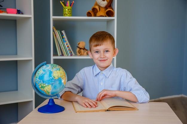 Uczeń chłopiec czyta książkę w szkole. koncepcja edukacji